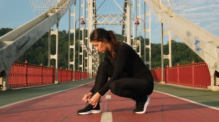 cadarço : Young athlete woman tying running shoes with earphones on the ground. Female runner ties sneakers before training on the bridge 4k