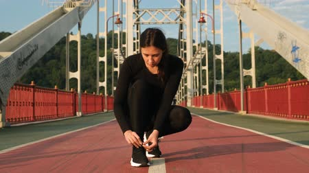 cadarço : Woman tying shoelace on sneakers on city bridge and starting to run. Female athlete ties running shoes before training 4k
