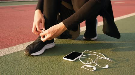 cadarço : Young athlete woman tying running shoes with earphones on the ground. Close up 4k