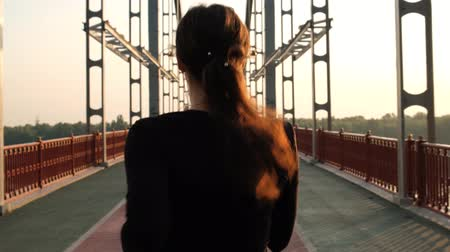 mosty : Slow motion scene of an athletic girl in black sportswear runs across the bridge during the sunrise time 4k Wideo