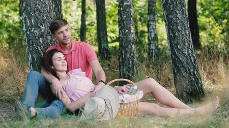 cesta de picnic : Picnic time. Happy young couple relaxing in the park. The man hugs his girlfriend and points his hand. Happy future allegory 4k
