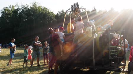goteras : A group of curious children surrounded a car with a gas installation for hot air balloon. Children near the balloon. Sunbeam leaks into the camera 4k