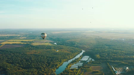 dirigível : Aerial view of a hot air balloons flies over the forest and river. Balloon festival. Fantastic summer sunset scene 4k Vídeos