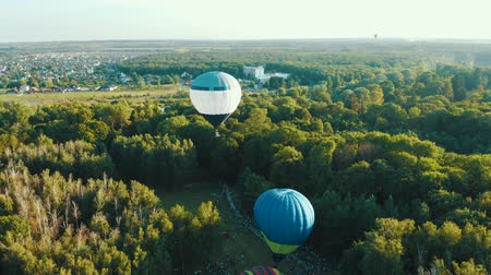 vzducholoď : Hot air balloons takes off among the trees in the park during the festival. Aerial view from above 4k Dostupné videozáznamy