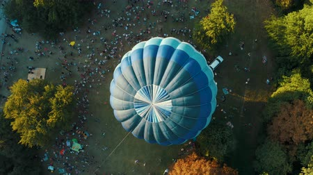 being prepared : Blue hot air balloon being prepared for a launch in the park. Aerial view from above 4k