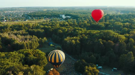 montgolfière : Hot air balloons takes off among the trees in the park at the sunset. Aerial footage 4k