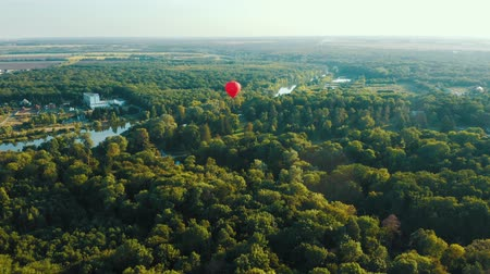 montgolfière : Aerial view of red hot air balloon flies over the trees. Sunset summer scene 4k