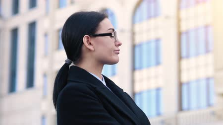 yüz buruşturma : Young confident woman in a business suit grimaces at the camera. Office building on the background 4k