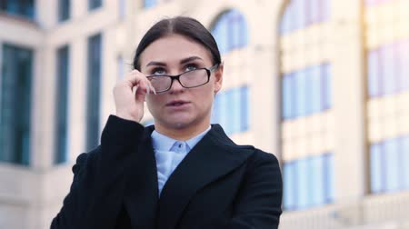 yüz buruşturma : Young business woman takes off glasses, grimaces, fooling around. Attractive brunette office employee outdoors 4k