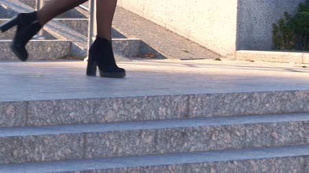 reporting : Young business woman in black skirt is late and run down of the stairs with documents in hands. Drops paper documents on the ground. Close up 4k Stock Footage