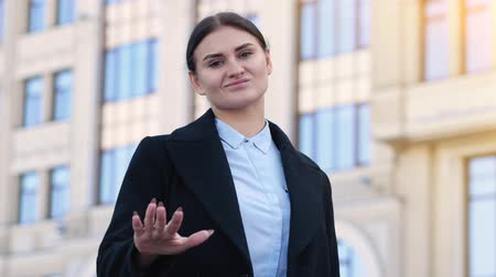 dubbioso : Young brunette woman shows waving sign for doubting. Office building on the background 4k