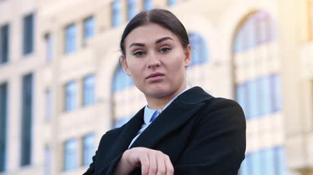 descontente : A young woman in a business suit is grimacing against the background of an office building. Disgruntled office worker pisses off his boss 4k