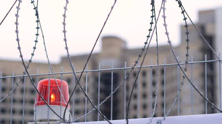 varovat se : Warning flashing alarm lights in a guarded area. Barbed wire fence on the background of an abandoned building 4k Dostupné videozáznamy
