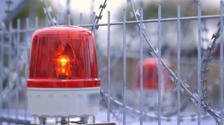 police sign : Red flashing emergency signal siren light rotating on barbed wired fence. Close up 4k Stock Footage