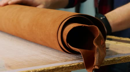 beige stof : A tanner unfolds a roll of leather on a table. Leather master choosing twisted piece of leather. Close up 4k