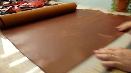 şifoniyer : A skinner unfolds a roll of leather on a table. Leather master choosing twisted piece of leather. Close up 4k