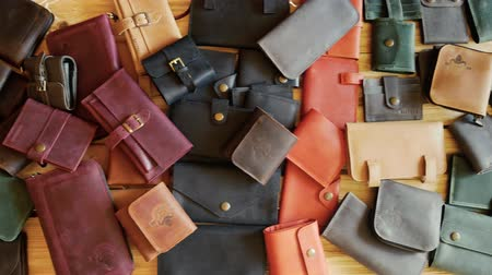 purse : Wallets of different colors laying on a wooden table. Crafted leather manufactures. Panoramic camera move 4k Stock Footage