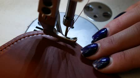 stiksel : Seamstress sews leather belt in a sewing workshop. Woman operates sewing machine. Top view 4k