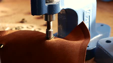 orlo : Female craftsman using press for installing metal eyelet on geniune leather product. Close up 4k