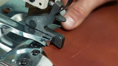 szewc : Craftsman using an automatic leather skiving machine. Skiving leather in a haberdashery manufactory. Splitting, aligning and cutting edge of leather details 4k