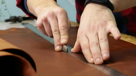 hasznosság : Young leather worker cuts off extra piece of leather with an utility knife. Craftsman at work. Close up 4k