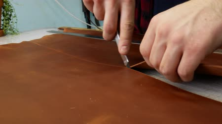 утилита : Man hand leather worker cuts off a piece of leather with an utility knife. Close up 4k