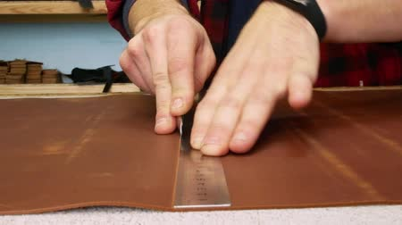 szewc : Craftsman cuts a sheet of genuine leather with an office knife. Handmade manufactures. Close up 4k