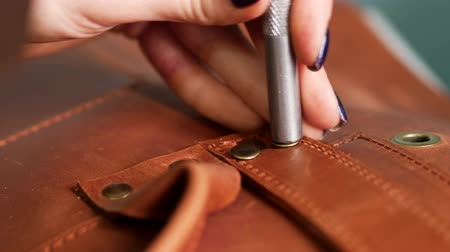 handig : Female worker puts rivets on leather bag straps with chisel and hummer. Crafted handmade manufactures. Close up 4k Stockvideo