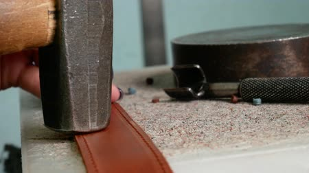 prik : Leather master makes holes in leather for fittings, rivets. Using a chisel and a hummer in order to puncture leather. Handmade leather manufacture 4k
