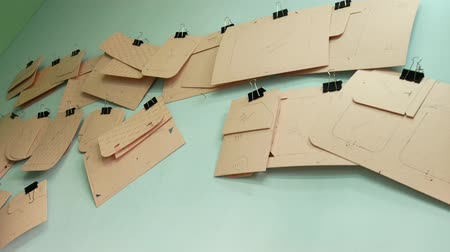 párat se : Paperboard billets for sewing bags hanging on the wall. Leather manufacture pattern 4k