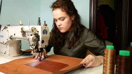шить : Brunette seamstress sews a pocket to a leather bag in a sewing workshop. A woman operates sewing machine 4k Стоковые видеозаписи