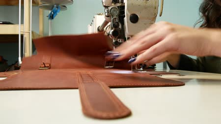 materials : A seamstress sews a pocket to a leather bag in a sewing workshop. A woman operates sewing machine. Slave work concept 4k