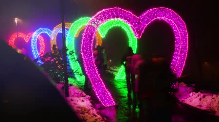 светящийся : Valentines Day. Neon hearts. The tunnel of lovers. Timelapse people are photographed near colored garlands in the shape of hearts 4k