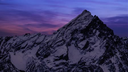 hilâl : Crescent descending down fast at sunset over the mountains covered with snow Stok Video