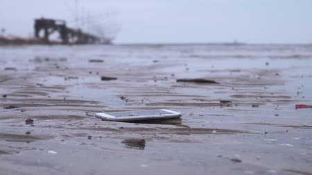 kap : Smartphone falls on the ground on the wet beach