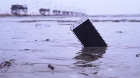 kap : Smartphone stuck in the sand of the sea