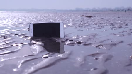 kap : Smartphone stuck in the wet sand of the beach Stock mozgókép