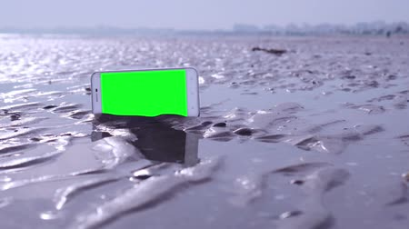 kap : Smartphone with green screen on wet sand