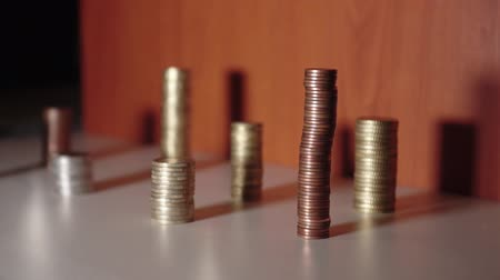 buy gold : Groups of coins on a table with a moving shadow