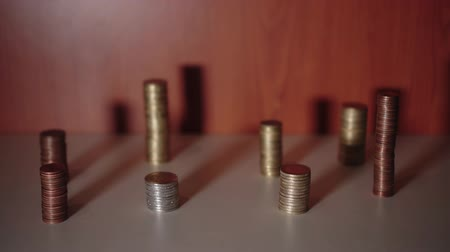 depósito : Groups of coins on a table with a moving shadow