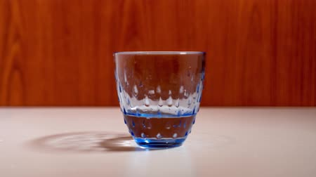 clear the table : Glass tumbler fills quickly with water Stock Footage