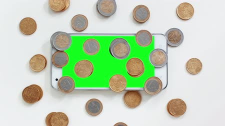 omkleden : Smartphone with green screen with coins around Stockvideo