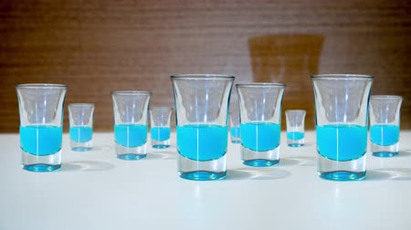 clear the table : Many glasses are filled with blue spirits