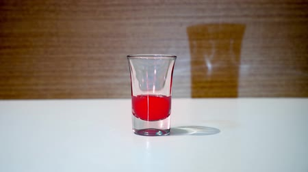 clear the table : Shot glass is filled with red liquid