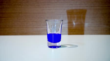 Shot glass is filled with blue liquid Vídeos