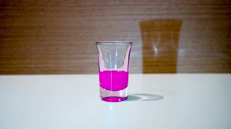 Shot glass is filled with pink liquid