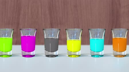 clear the table : Shot glasses are filled with alcohol of different colors Stock Footage