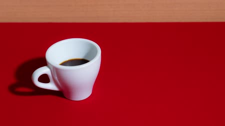 biała czekolada : Coffee fills the cup in stop motion on the red table Wideo