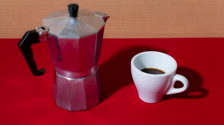 Coffee fills the cup in stop motion on the red table Vídeos