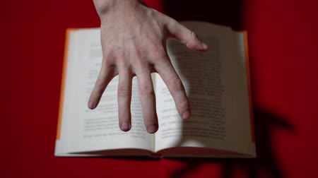 The hand browses through the pages of the book with telekinesis 動画素材
